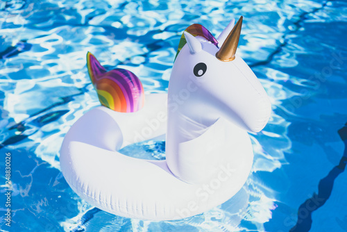 Cadres-photo bureau Flamingo Inflatable colorful white unicorn at the swimming pool. Vacation time in the swim pool with plastic toys. Relaxation and fun concept. Ripple Water in swimming pool with sun reflection