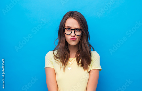 people concept - frowning young woman or teenage girl in yellow t-shirt and glas Wallpaper Mural