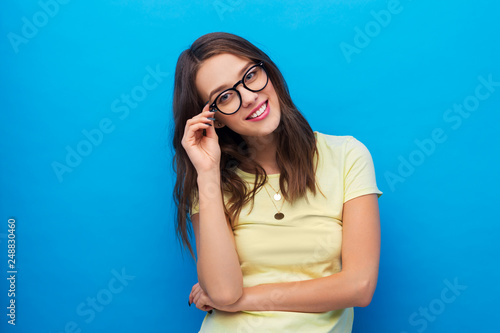 people concept - smiling young woman or teenage girl in yellow t-shirt and glasses over bright blue background