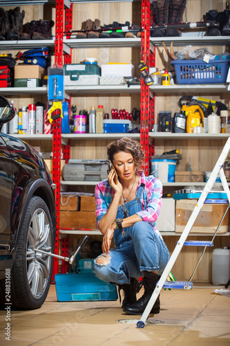 Photo woman in blue denim overall talking on the smartphone near the car in the garage