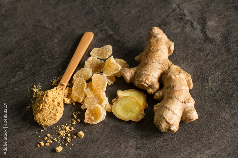 Fotografia Ginger root, candied and ginger powder in wooden spoon over grey concrete backgr