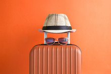 Luggage With Woven Beach Hat And Sunglasses On Orange Background Minimalistic Vacation Concept