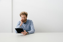 Thirty Something Bearded Man Looking Thoughtfully On His Tablet Sitting At An Empty Light Colored Desk.
