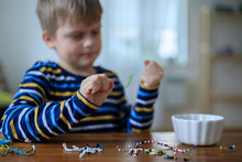 Boy Is Designing Toys From Multicolored Beads At Home