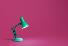 Retro Green Desk Lamp Turned On And Bent Over Shining On A Bright Pink Background.  Landscape Orientation With A Left Side Composition Leaving Room For Text And Copy Space.