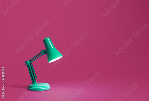 Photo Retro green desk lamp turned on and bent over shining on a bright pink background