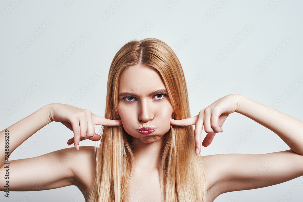 Fototapety, obrazy: Studio shot of stubborn young blonde woman blowing cheeks and feeling mad. Human emotions.