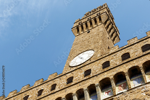 Color DSLR image of the historic landmark Tower of the Palazzo Vecchio, Florence, Italy, against a blue sky. Vertical with copy space for text