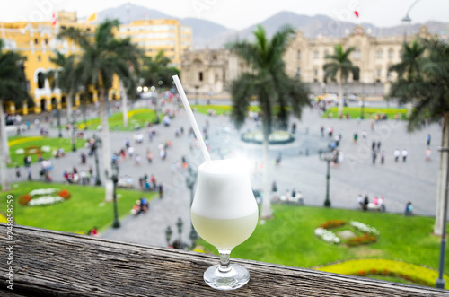 Pisco sour homemade cocktail with the background of the main square of Lima - Pe Canvas Print