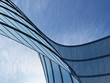 Leinwanddruck Bild - 3D stimulate of high rise curve glass building and dark steel window system on blue clear sky background,Business concept of future architecture,lookup to the angle of the corner building.