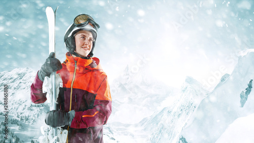 Fotografie, Tablou Female skier standing with skies in one hand on background of beautiful mountain landscape