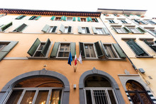 Outside Exterior Florence Building In Firenze, Tuscany Italy On Empty Alley Street In Morning Wide Angle View Looking Up With Flags
