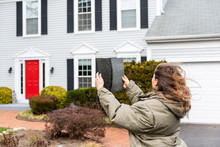 Young Woman Female Homeowner Standing In Front Of House On Windy Day In Coat Jacket During Winter Storm Holding Up Roof Tile Shingle Inspecting Damage