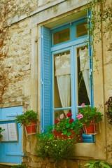 Fototapeta na wymiar Finestra con imposte azzurre e fiori, Costa Azzurra in Provenza, Francia