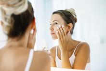 Woman Applying Face Cream In B...