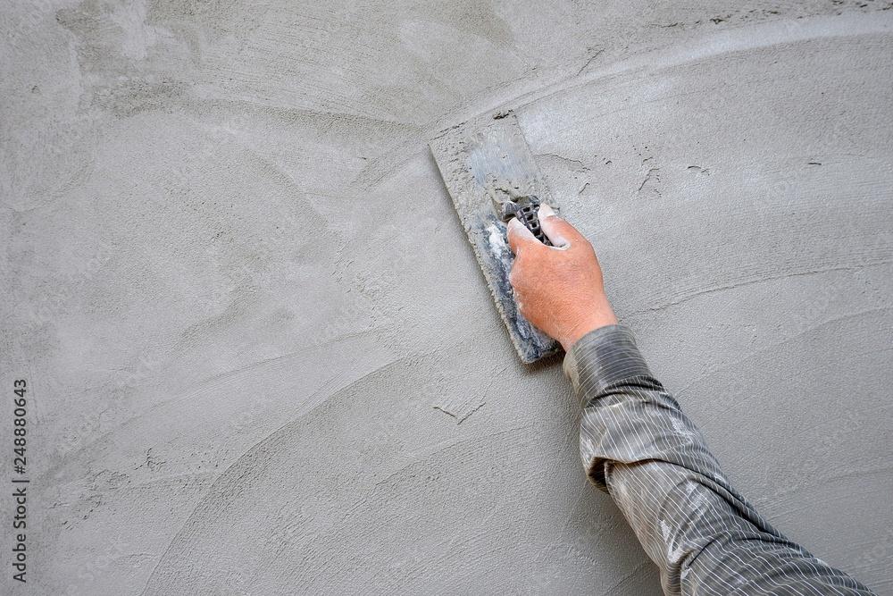 Fototapeta Plasterer man hand using trowel to plastering cement on concrete wall