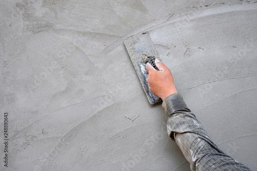 Fototapeta Plasterer man hand using trowel to plastering cement on concrete wall  obraz