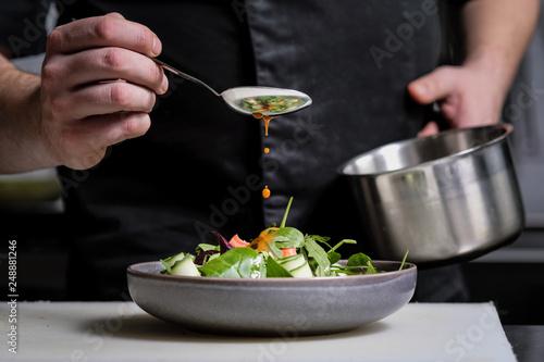 Obraz na plátně Close-up of the hands of a male chef on a black background