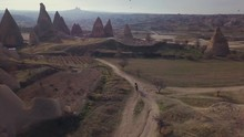 Top Down Drone Shot Following A Horse Rider, On A Dusty Deserted Path, Among Chimney Rocks, To Unknown, In Cappadocia, Nevsehir, Turkey