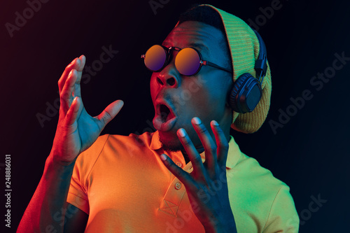 Fotografie, Obraz  Young handsome serious sad hipster man in sunglasses listening music with headphones at black studio background with neon lights