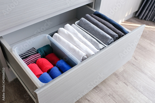 Foto  Close up stack of folded t shirt black gray white color and folded bright colorful socks in plastic baskets in a closet drawer in natural light