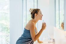Woman Brushing Teeth With Wate...