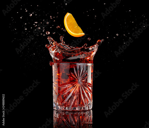 orange slice falling into a splashing negroni isolated on black
