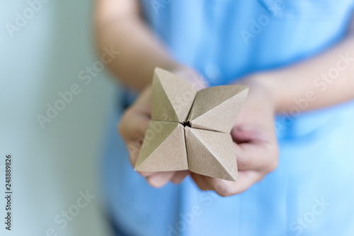 Fotografia, Obraz  Woman's hands holding a paper fortune teller on blue background