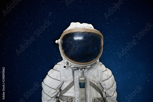 Fotografie, Obraz  Soviet cosmonaut or astronaut or spaceman suit and helmet on black space with st