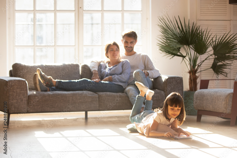 Fototapety, obrazy: Happy parents relaxing on couch while kid drawing on floor