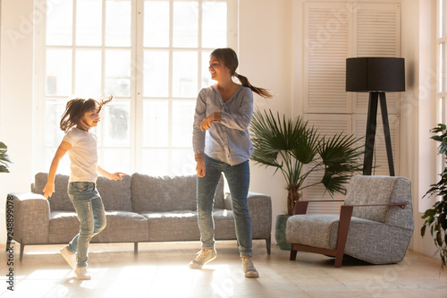 Fotografía  Joyful mother with child girl having fun dancing at home