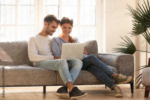 Fotografía  Millennial happy couple using laptop doing online shopping, ecommerce
