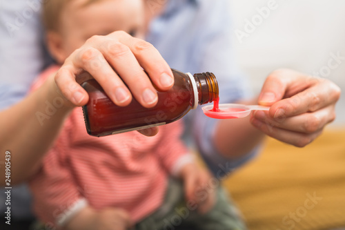 Carta da parati close up of mother pouring cough syrup