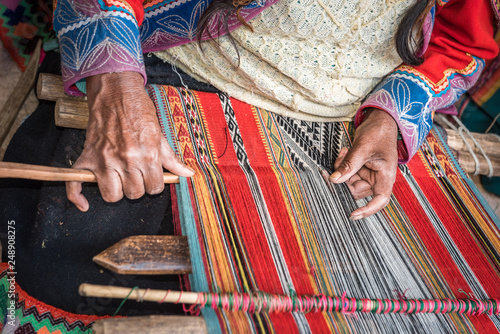 Photo Hands of Peruvian weaver making a striped textile