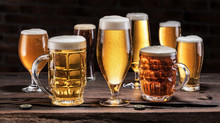 Cold Mugs And Glasses Of Beer On The Old Wooden Table At The Black Background. Assortment Of Beer.