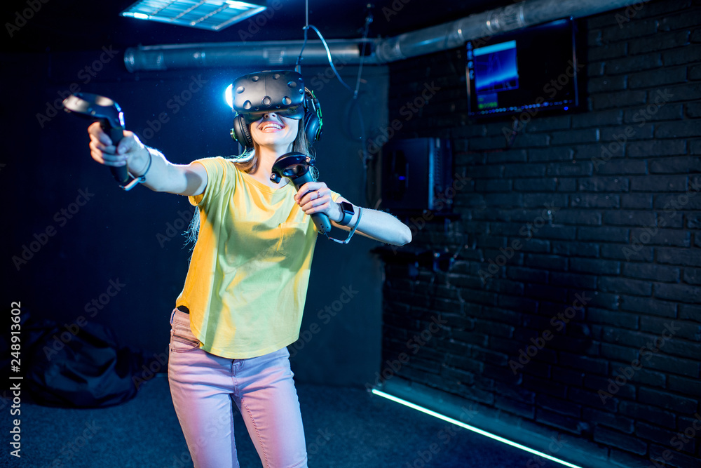 Fototapeta Young woman playing game using virtual reality headset and gamepads in the dark room of the playing club