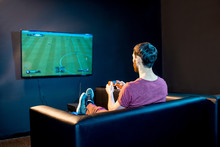 Man Playing Football Game With Gaming Console Sitting On The Couch In Front Of The Monitor At Home Or Playing Club
