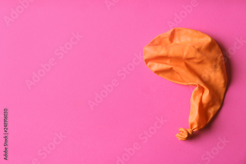 Orange deflated balloon on color background, top view with space for text - 248916030