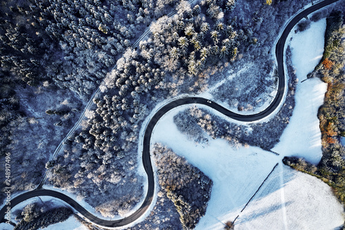 Fotografie, Obraz  Aerial drone view of a curved winding road through the forest up in the mountain