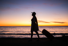 Traveling, Beach And Holiday Concept - Female Silhouette Walking Along Ocean Coast Pulling Suitcase