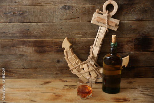 Poster Affiche vintage glass and a bottle of old whiskey on the background of an anchor made of wood on a wooden oak background with space for text