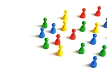 Game Figures From A Board Game In Different Colors Stand On A White Background And Throw All The Shadows In One Direction - Concept With Different Figures On White Background