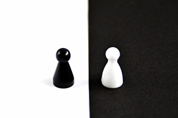 A black pawn stands in front of a white background and vice versa - concept with strong contrasts as a symbol of differences and equality, as well as ying and yang