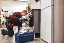 Whats Up With Oven. Full Length Of Repairman Examining Oven