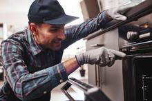Don't Delay With Repair. Close-up Of Repairman Examining Oven