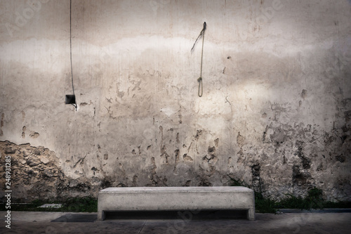 Fotografie, Obraz  Concrete bench in front of abandoned wall with hangman knot hanging at the wall,