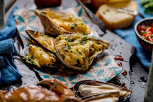 Baked Oysters With Cheese And Other Seafood With Glasses Of Beer On The Table
