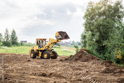 Fotografie, Obraz large yellow wheel loader aligns a piece of land for a new building