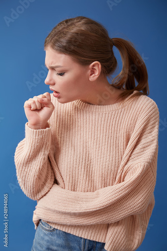 Fotografia  Young ill woman coughing on isolated background, sore throat