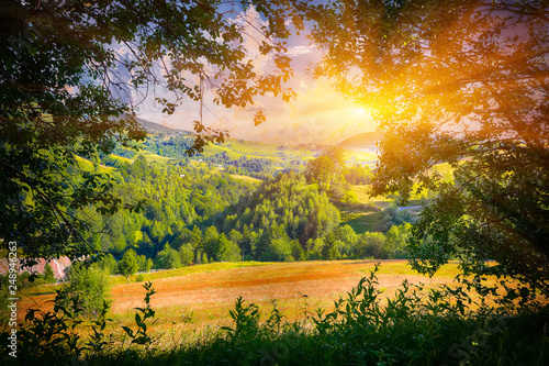 Beautiful countryside landscape with forested hills and haystacks on a grassy rural field in mountains
